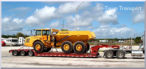 A large, bright yellow dump truck on a flatbed trailer on a sunny day