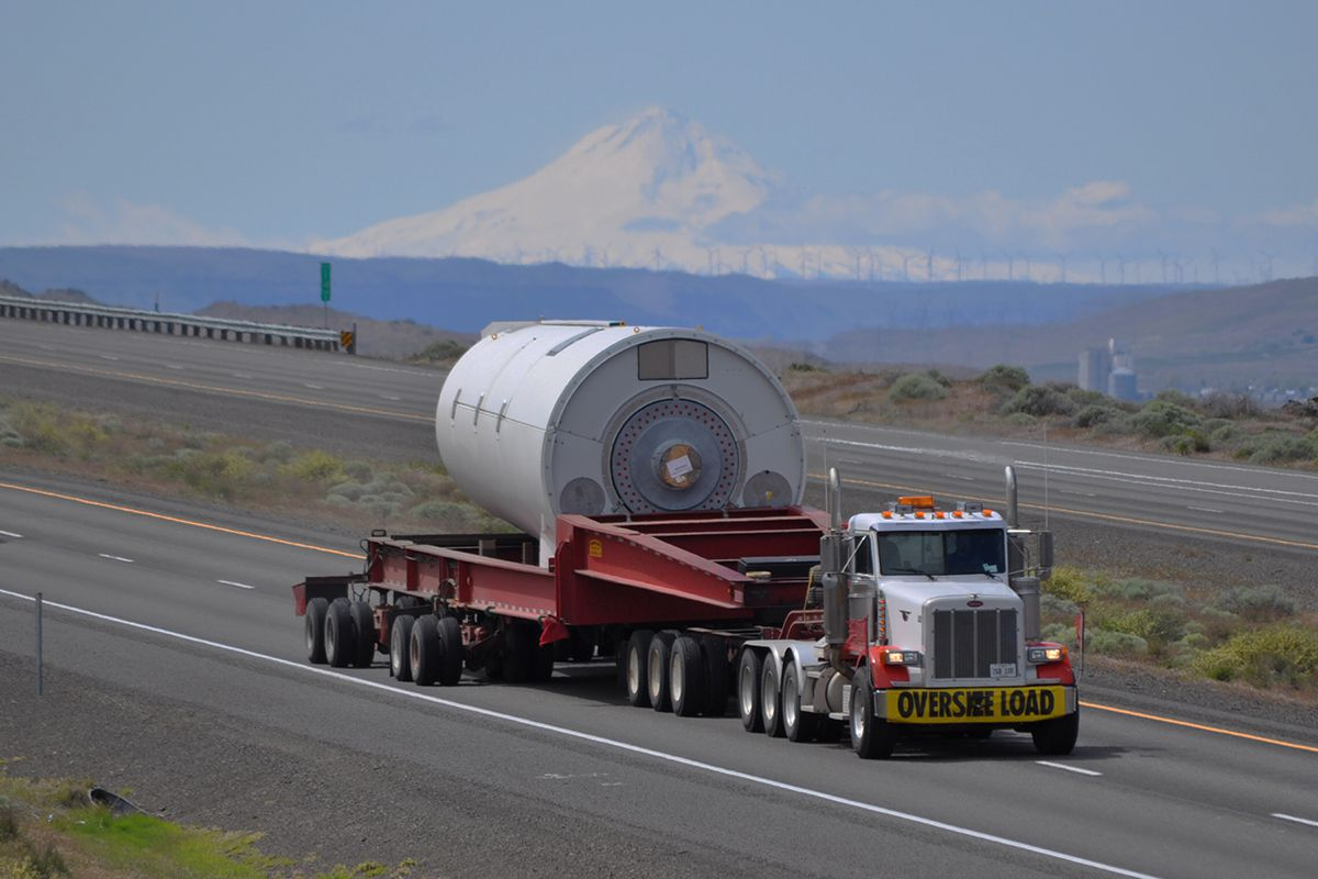 Image of a truck carrying an specialized freight load of a section of a solid rocket booster.