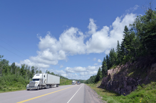 beautiful mountain road and a white truck driving down a 2 lane highway on a sunny day