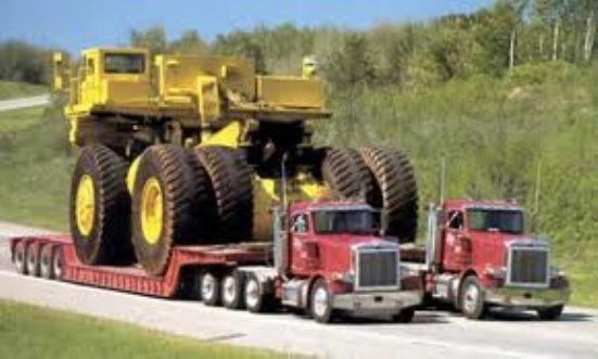 2 specialized freight truck side by side both have a earth mover on their trailers.