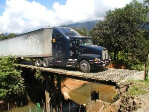 Semi Truck Transporting Freight Over a Rural Bridge