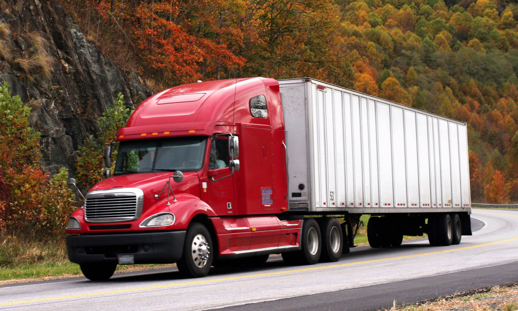 a semi truck traveling down the road in the fall, the background is full of trees in there brilliant autumn colors