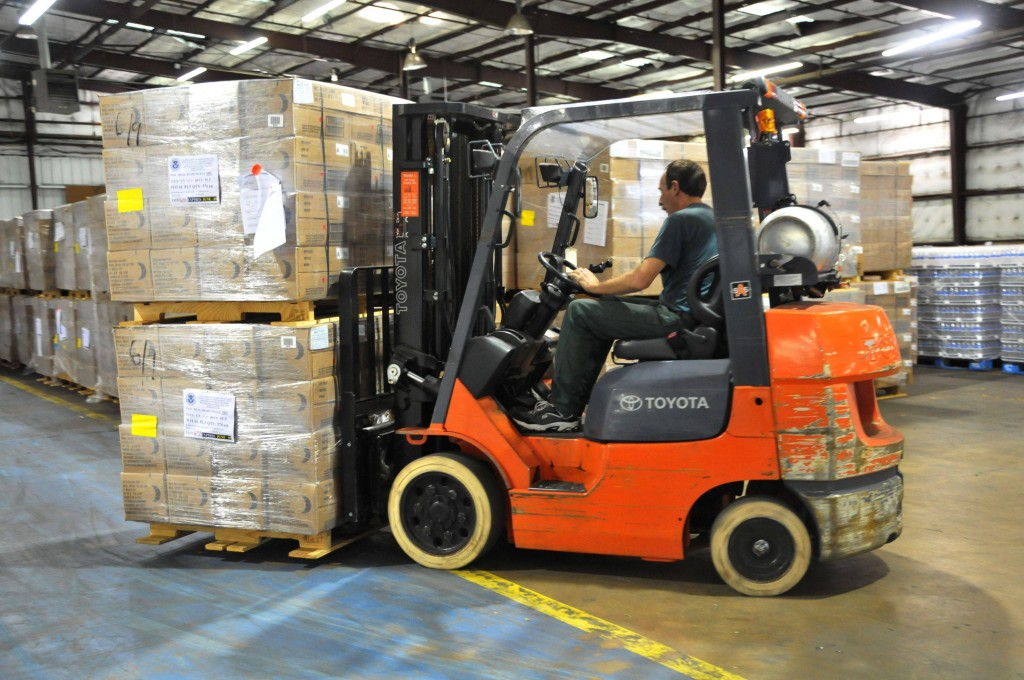 Image of a man on an orange forklift in a warehouse lifting 2 stacked pallets.