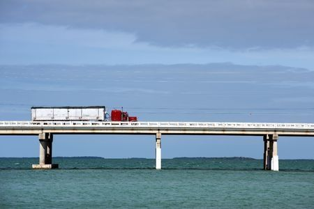 A semi truck with trailer crossing a very long bridge ove blue, blue water on a sunny day