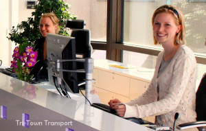 An image of our 2 receptionists at tritown transport, they are both blonde and very attractive, they are smiling and looking at the camera