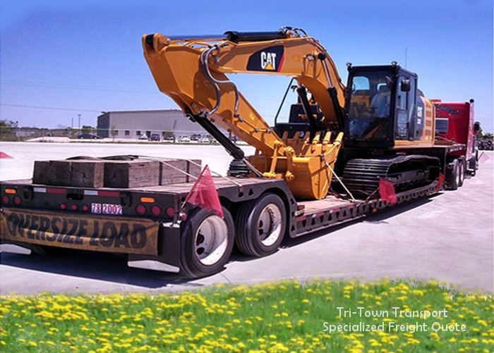 A backhoe on a flatbed trailer in front of a field of yellow flowers on a sunny day