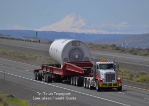 Image of a semi pulling a flatbed trailer with an oversized- or specialized load, it's a sunny day and a snow capped mount rainier is in the background