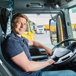 Specialized & Oversized Freight Rates - Happy Truck Driver Holding Steering Wheel
