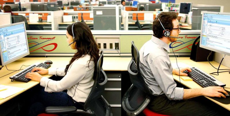 an image of 2 dispatch employees back to back seated and facing their monitors with phone headsets on. One is a man and one is a woman