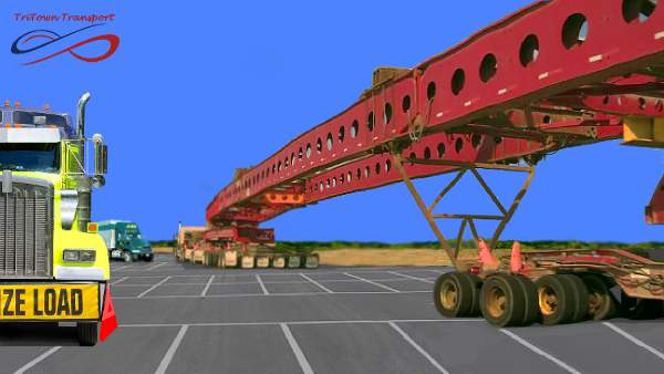An image of an over-sized freight load, it's 2 very long metal beams or roof spans they are in a parking lot and the tractor is in the distance and the span is close to the camera
