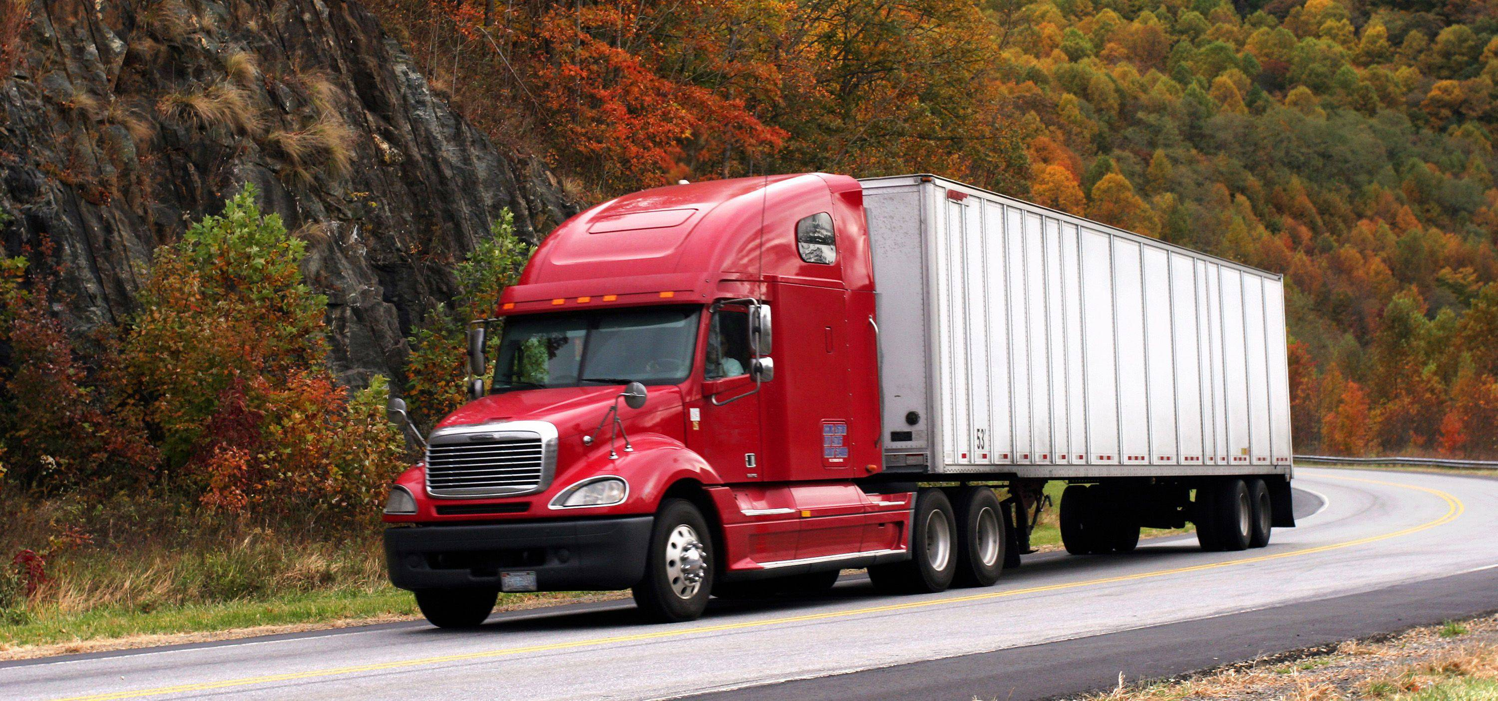 Image of a red semi tractoer and silver trailor going down amountian road in the Fall and the leave are a thousands of shades of red and yellow and gold and orange it's a beautiful image