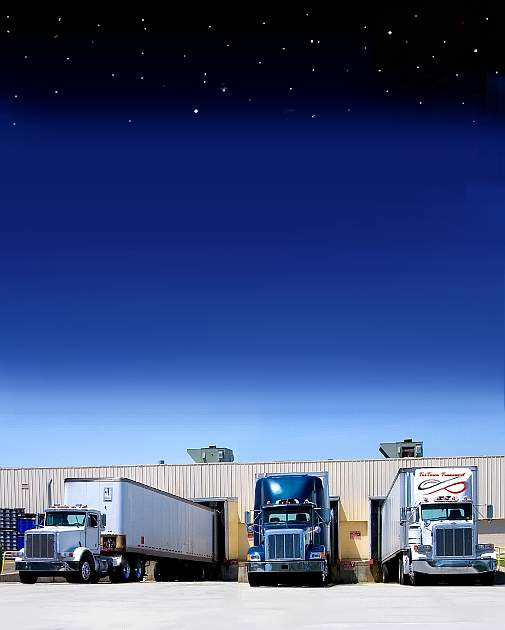 An Image of 3 semi trucks backed into docks for loading at the bottom are the trucks then above them is a blue sly gradually getting darker until black with stars.