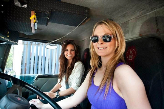 an image of 2 attractive semi truck drivers in the cab of a truck one has long blonde hair and one woman has brunette hair the blonde is wearing sunglasses they are both wearing tank tops and smiling at the camera