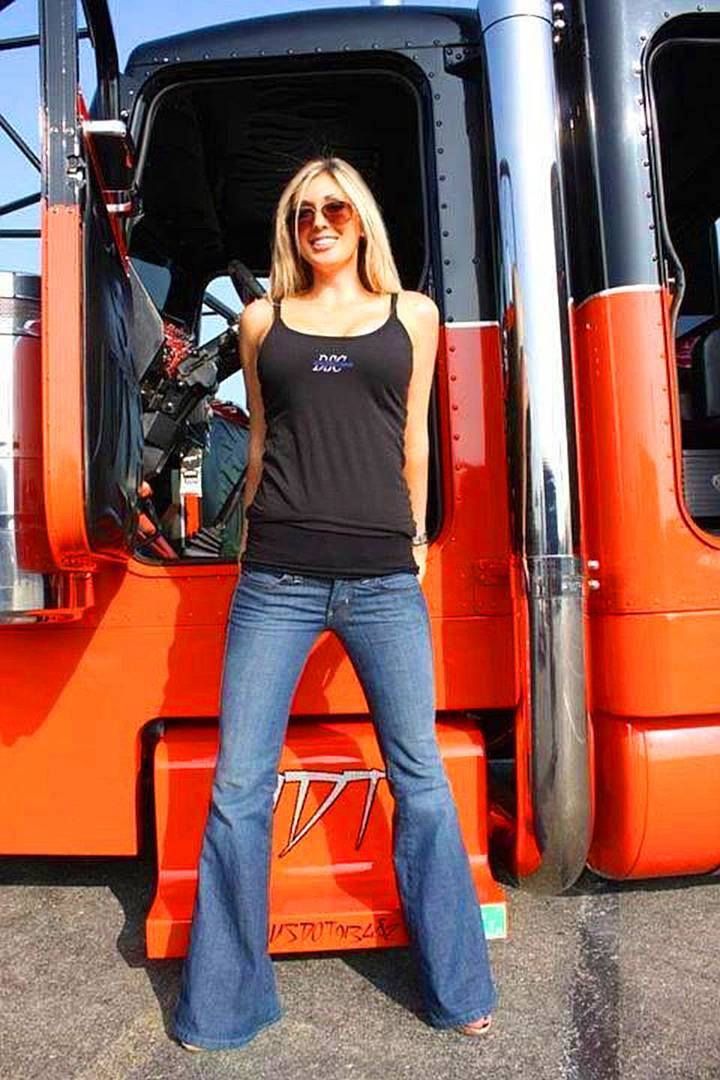 an image of a tall woman with long blonde hair wearing blue jeans and a black tank top. She is standing in front of her semi.