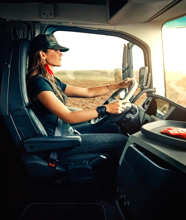 image of an attractive young woman wearing a baseball cap and driving a semi tractor trailer, it's a sunny day she is looking out the windshield, she is very thin wearing a black t-shirt and blue jeans, she's very beautiful.